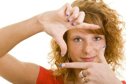 Junge rothaarige Frau bildet mit ihren Fingern ein Rahmen vor ihrem Gesicht