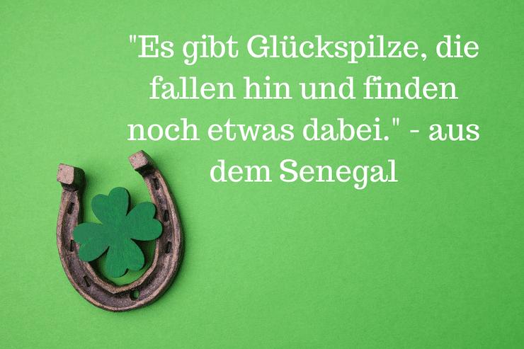 """4 blättriges Kleeblatt mit Hufeisen mit dem Spruch: """"Es gibt Glückspilze, die fallen hin und finden noch etwas dabei."""" - aus dem Senegal"""