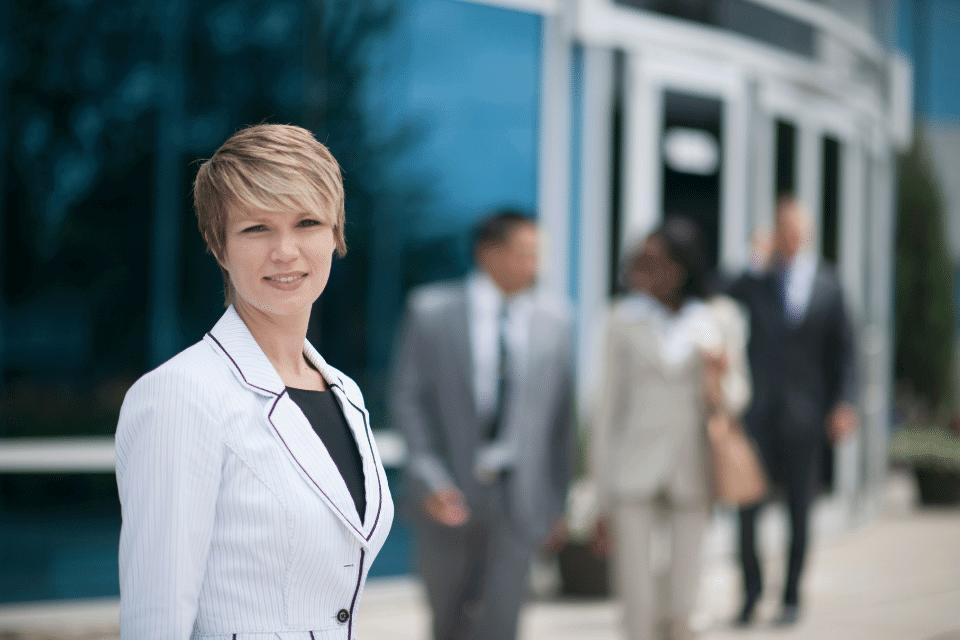 Eine glückliche Frau steht im Vordergrund - Assoziiere glückliche Menschen