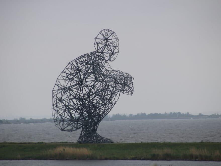 Metallskulptur schaut aus Meer hinaus - Das Gesetz der Anziehung gehorcht mir