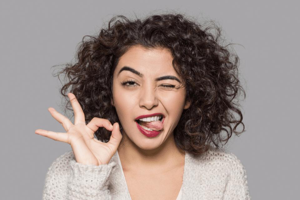 Eine Frau macht ein okay Zeichen und strekt schadenfreudig ihre Zunge quer heraus - Der Mensch ist nicht autonom und kann nicht alles kontrollieren