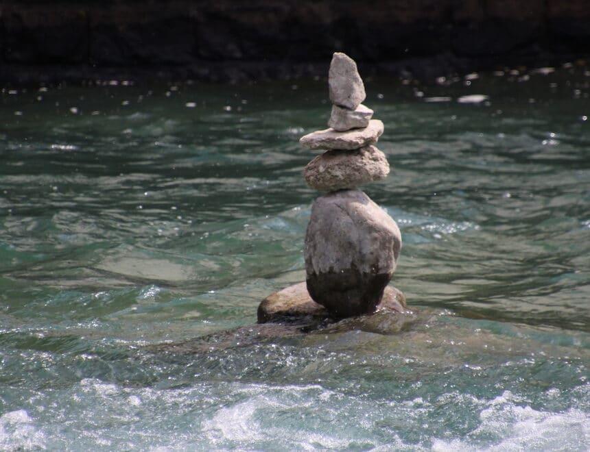 Leben Loslassen lernen- Steine im Fluss symbolisch aufeinander aufgestapelt