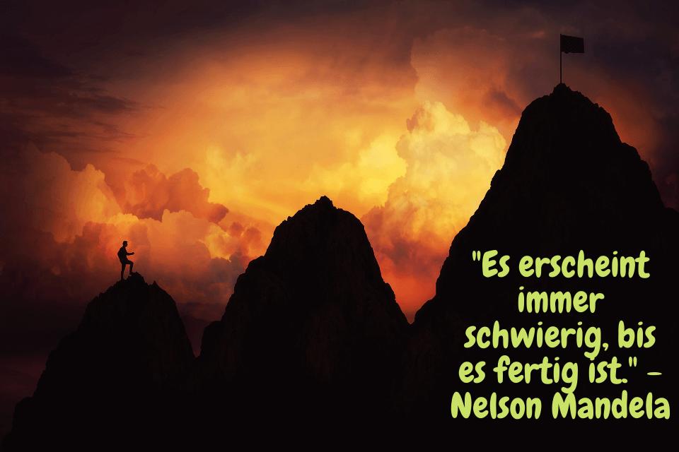 """Ein Mann beim Bergsteigen mit dem Zitat : """"Es erscheint immer schwierig, bis es fertig ist."""" - Nelson Mandela"""