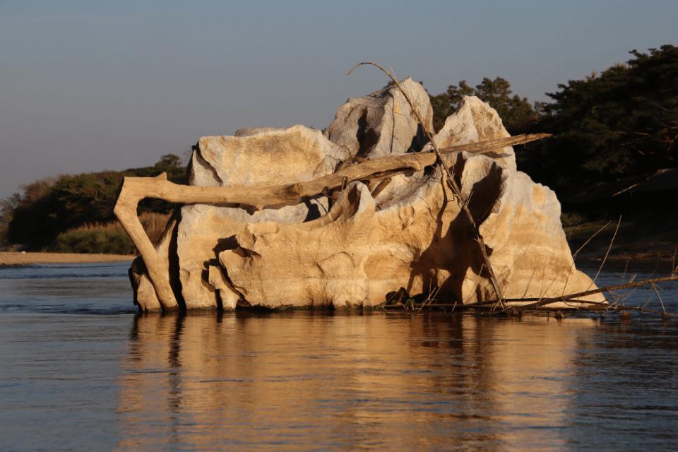 Flussrand mit blick auf einen grossen Stein