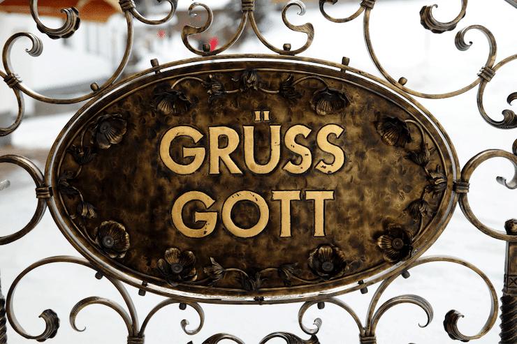 Ein Schild am Eingangstor mit der Aufschrift Griass Gott