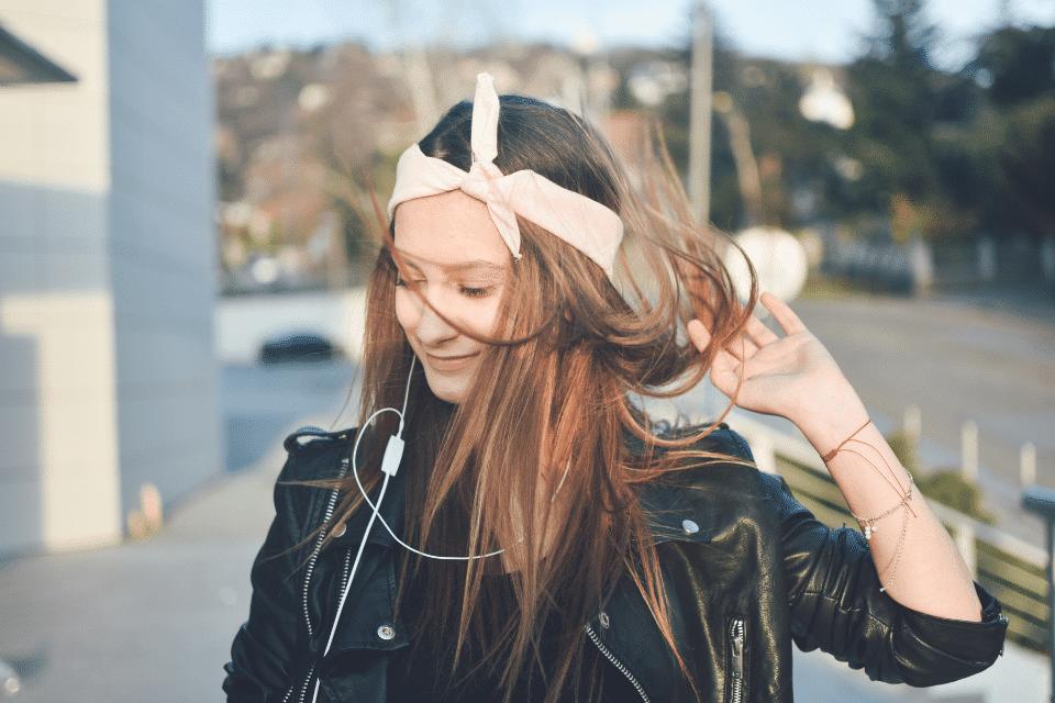 Eine jung Frau hört Musik beim spazieren und ist glücklich