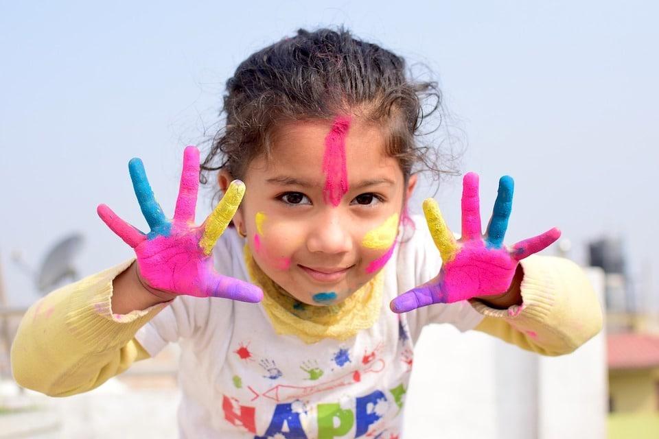 Junges mädchen mit bunt bemalenen Händen und Gesicht - Lustige Werbung mit Kindern