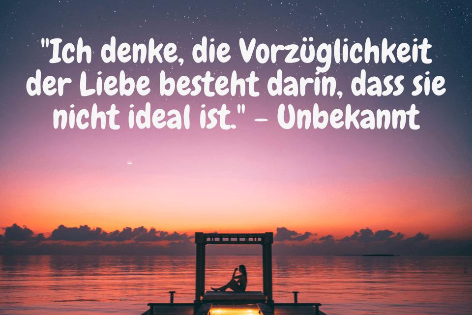 """Frau sitzt bei Sonnenuntergang am Meer mit Zitat: """"Ich denke, die Vorzüglichkeit der Liebe besteht darin, dass sie nicht ideal ist."""" - Unbekannt"""