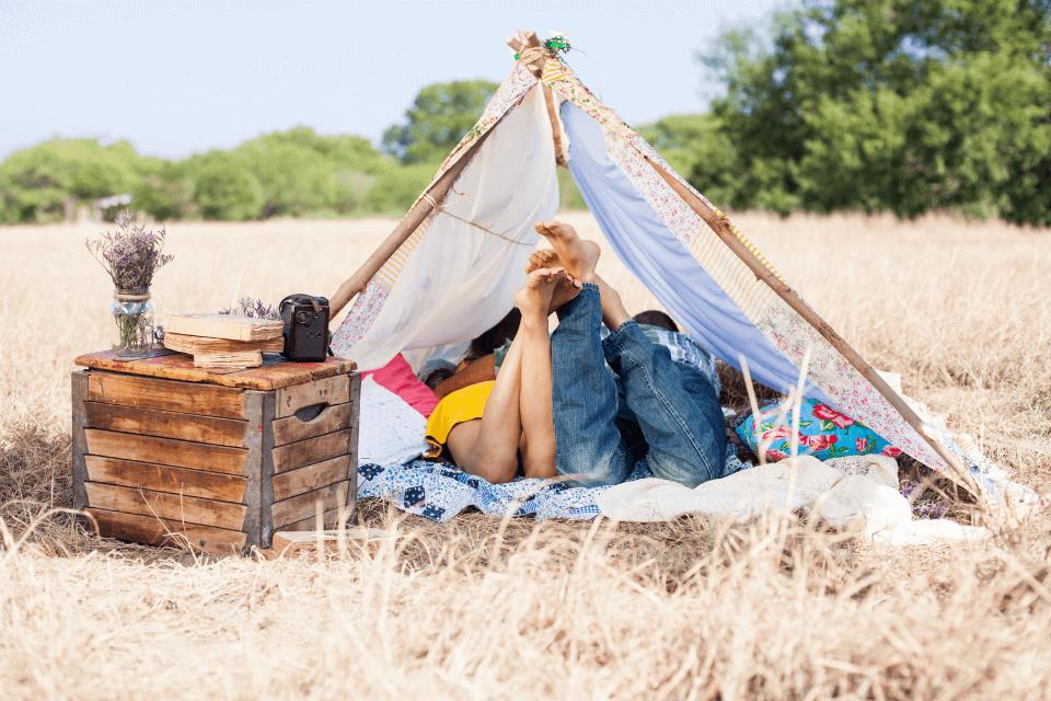 Ein Paar liest ein Buch in einem selbst gebastelten Zelt auf einem Zelt. Eine alte Holzkiste dient als Abstellfläche für eine Kamera, Bücher und einer Blumenvase mit gesammelten Blumen - in der Natur herumhängen