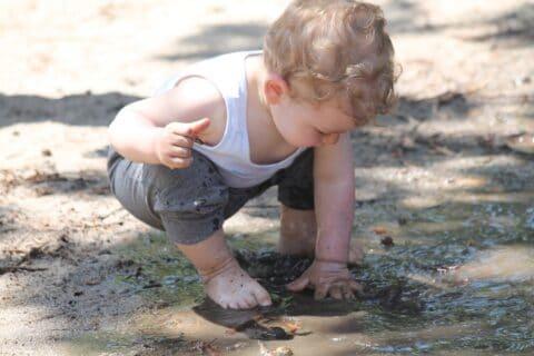 Kind spielt Pfütze