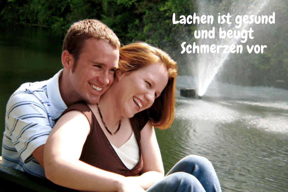 Ein Mann umarmt eine Frau und beite sind am Lachen - Lachen ist gesund und beugt Schmerzen vor