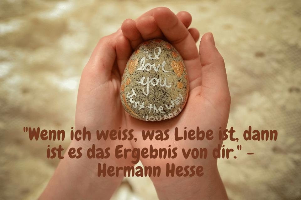"""Ein Stein aufliegend in den Händen mit der Aufschrift: """"Wenn ich weiss, was Liebe ist, dann ist es das Ergebnis von Dir."""" - Hermann Hesse"""