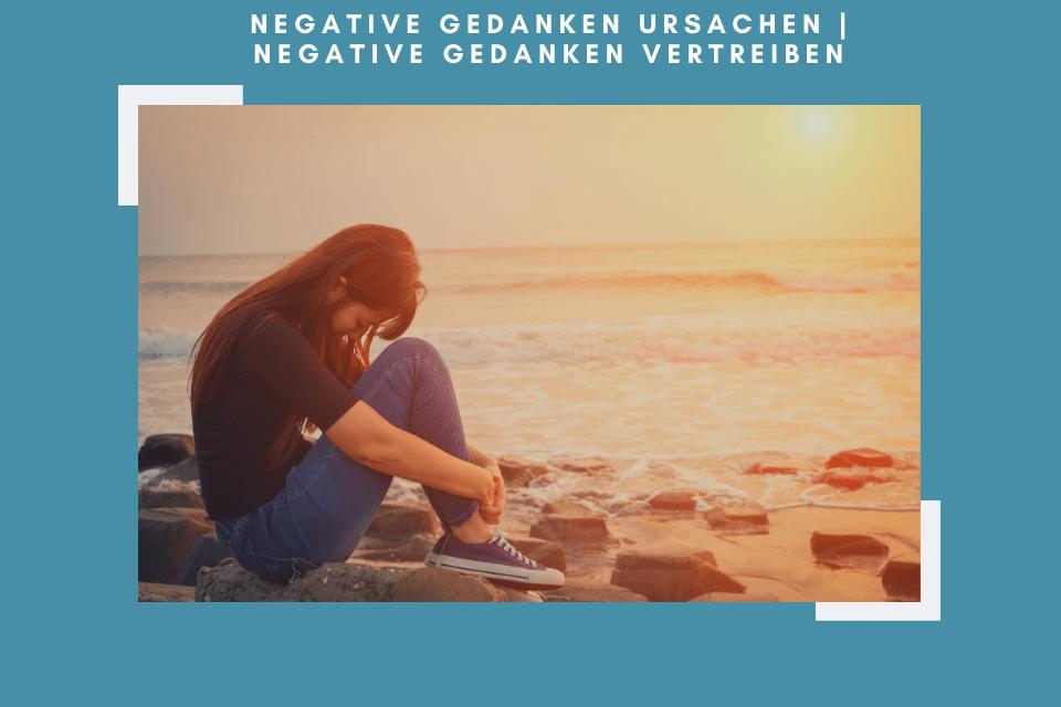 Negative Gedanken - Frau sitzt mit gesenktem Kopf am Meer und macht sich negative Gedanken.