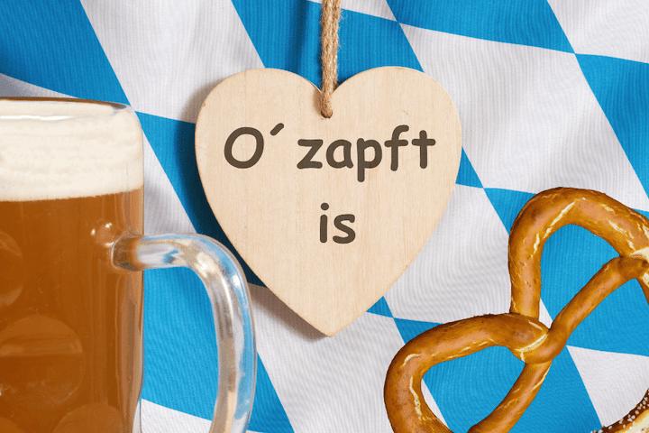 """Ein Bierkrug mit einem Bretzel -und der Aufschrift: """"Ozapft is's"""""""