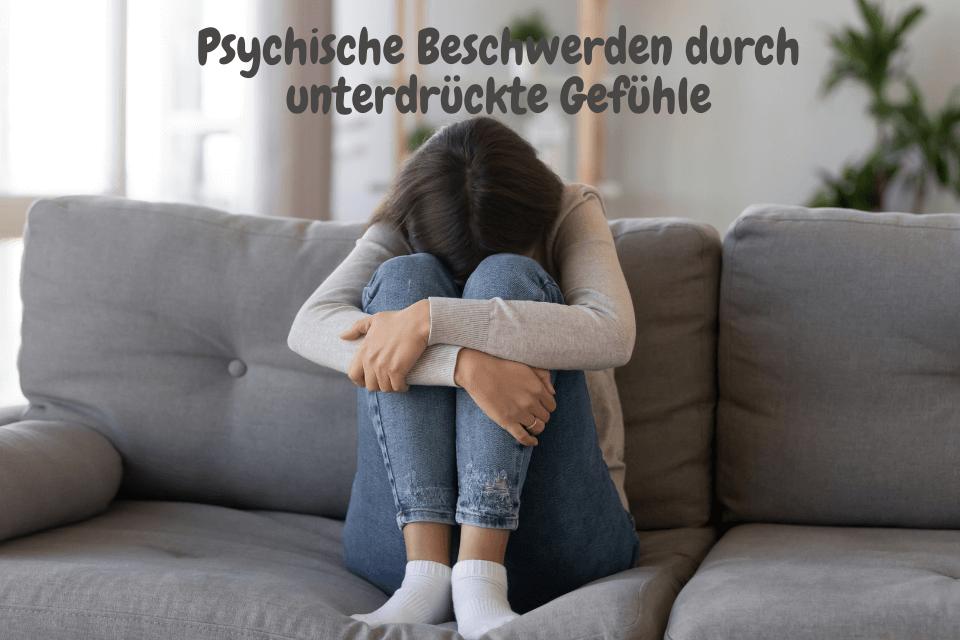 Eine Frau sitzt zusammengerugelt auf dem Sofa - Psychische Beschwerden durch unterdrückte Gefühle