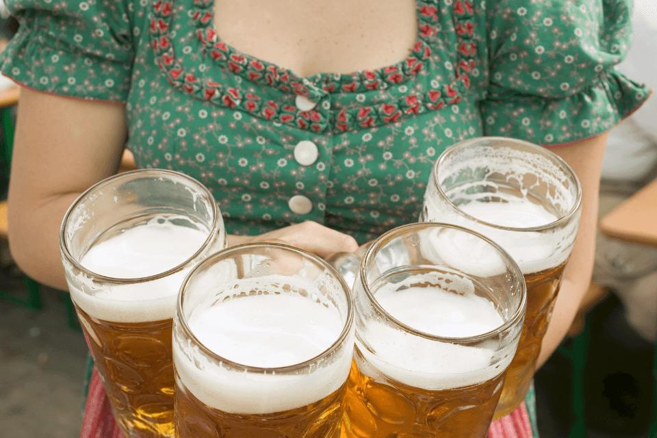 Frau trägt vier Seidla - Biergläser