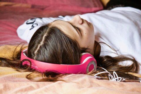 Mädchen hört Entspannungsmusik zum Einschlafen