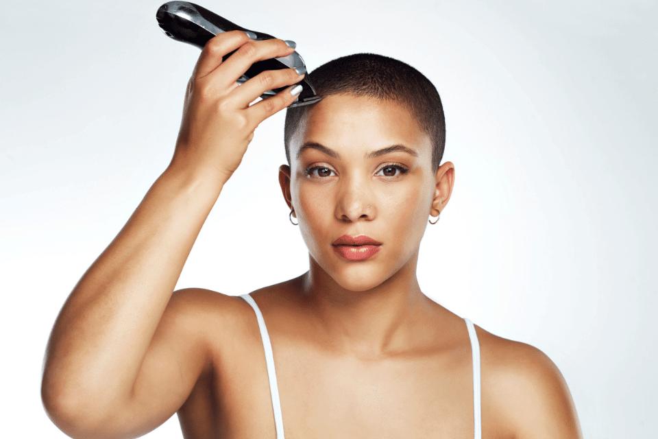Eine junge Frau schneidet sich mit einem Rasierapparat eine Glatze - Überrasche Dich mit etwas neuem
