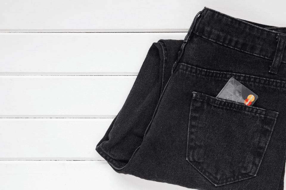 Eine Kreditkarte im Sack einer Jeans - Symbol für - Vernünftig Geld ausgeben