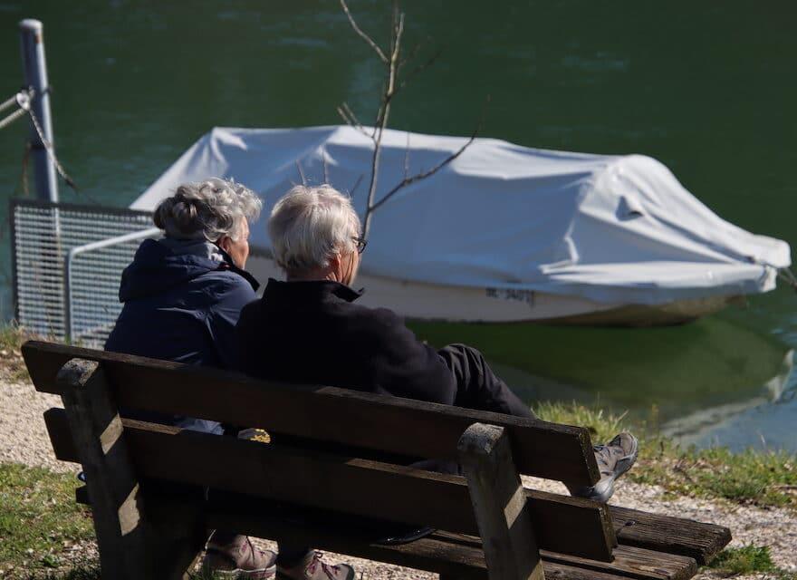 Zwei ältere menschen sitzen auf einenr Bank am Fluss und stellen sich die Frage - Wünsche manifestieren - wie manifestiere meine Wünsche?