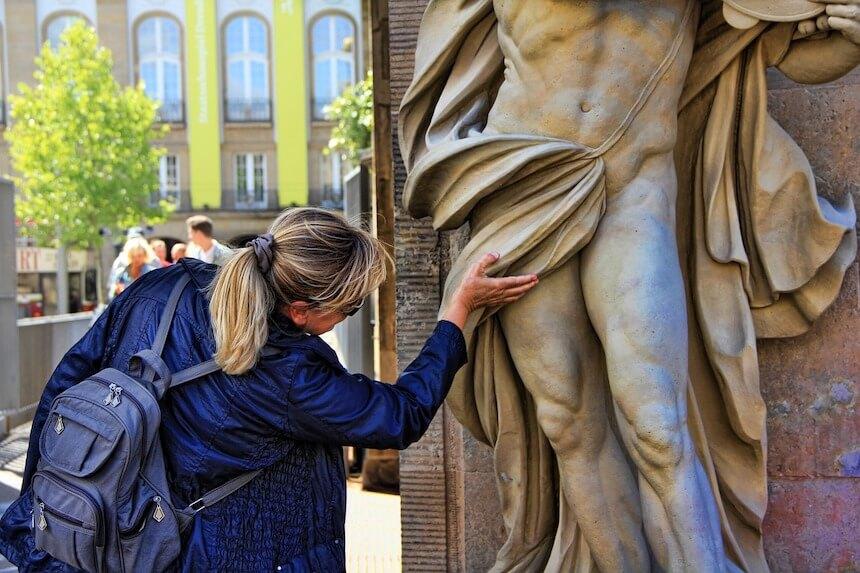 frau begutachtete eine männliche Statue